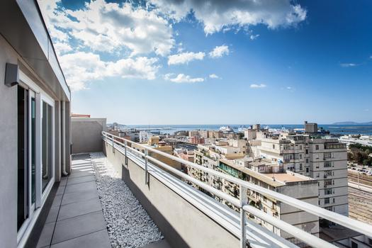 Sweeping view of the city and continuity of material through space for the Casa SG at Cagliari